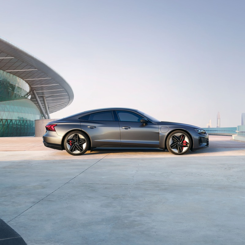 Audi RS e-tron GT sports car on a concrete surface in front of futuristic architecture.