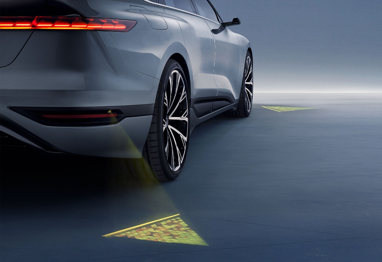 LED projectors on the vehicle create glowing triangles on the ground.