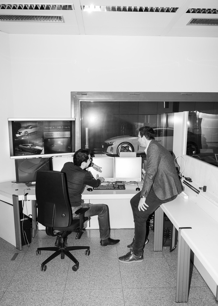 Dr. Kentaro Zens and Thomas Redenbach in discussion in front of a number of computer screens, with the Audi RS e-tron GT behind a window in the background.