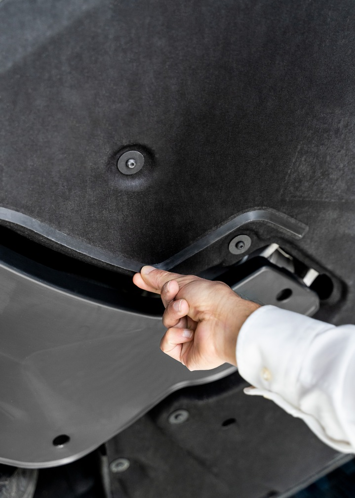 A hand indicates a plastic lip on the vehicle underbody.